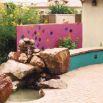 Colorful Screen Wall and Seatwalls with Waterfall at Brick Patio