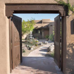 Wooden gates at masonry entry arch with flagstone path