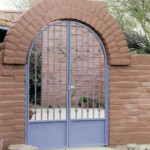 Custom ornamental iron gate at arched masonry entry