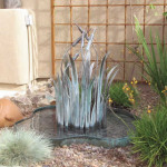 Copper cattail fountain with ornamental iron trellis and low maintenance plantings