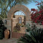 Arched entry in slump block wall with custom ornamental Iron Gate