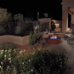 Gas fire pit and assorted lights illuminate outdoor living area